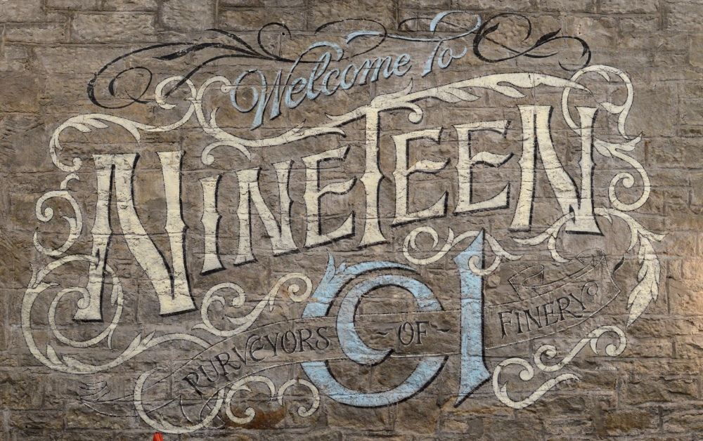 Hand-lettered sign on the wall by sign painter Ash Willerton